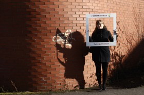 Woman standing against a brick wall, her shadow visible on the wall next to her. She is holding a large frame on which is written #GenderLightbulb