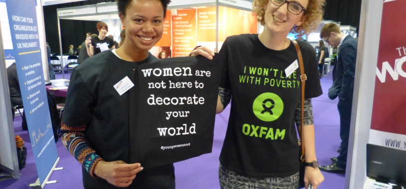 Two smiling women stand holding up a black tote bag on which is written 'women are not here to decorate your world'. One woman is wearing an Oxfam t-shirt that reads 'I won't live with poverty'