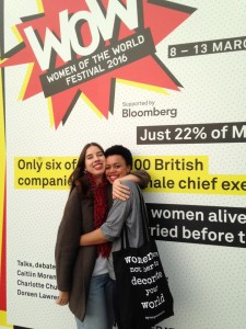 Two women hugging in front of a poster for WOW London