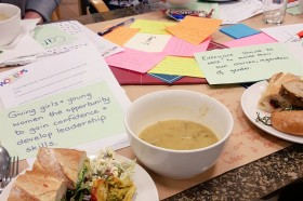 A table covered with pieces of paper, varying sizes and colours. A plate of sandwiches and a bowl of soup is in the forefront.