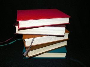A stack of hardcover books against a black background