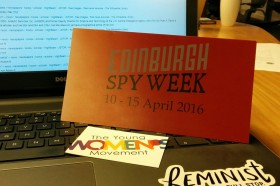 Picture of a laptop screen with a Spy Week pamphlet on the keyboard