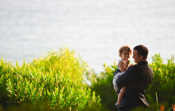 Dad holding daughter by a lake