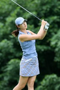 A woman holding a raised golf club against a backdrop of trees