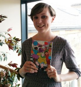 Gill Hatcher holds up an issue of Team Girl Comic