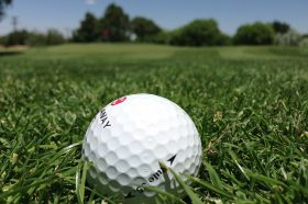 Close up of a golf ball lying on the green, with the horizon and blue skies in the background.
