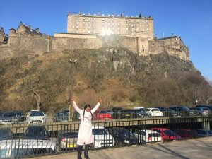 Angele Tomo posing with the Edinburgh Castle behind her.