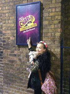 Hannah Howland poses with a sign for Charlie and the Chocolate Factory