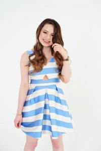 Estelle Maskame posing in blue and white striped dress.