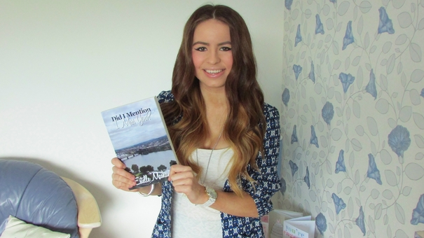 Estelle Maskame holds up a copy of her book, Did I Mention I Love You