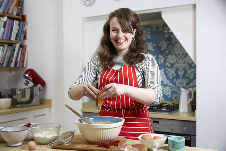Flora Shedden in the kitchen, cracking eggs in a red apron.