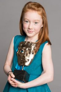 Cherry Campbell posing with her BAFTA award