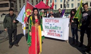 Roza Salih wearing Kurdish dress standing in front of a 'Scottish Solidarity with Kurdistan' banner