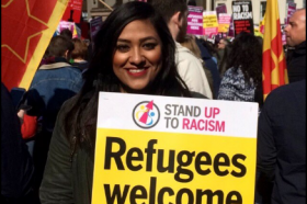 Suki Sangha holding a 'refugees welcome here' sign at a rally.