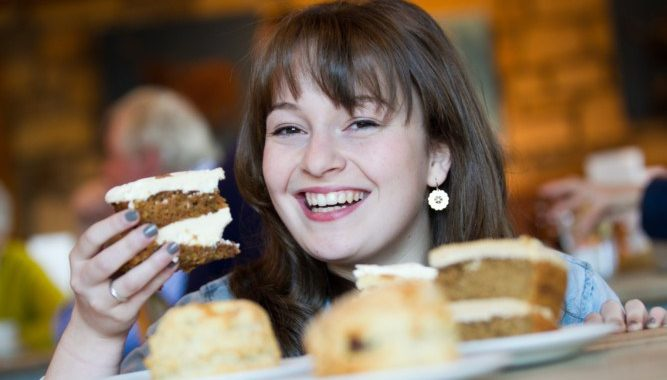 Flora Shedden poses with an array of baked goods in the foreground, holding a slice of cake.