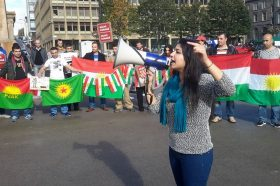 Roza Salih speaks to a rally with a megaphone